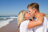 Middle aged couple kissing on beach — Stock Photo