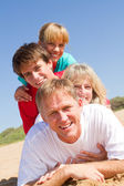 Happy family lying on beach — Stock Photo