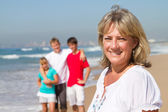 Happy mid age mother and family on beach — Stock Photo