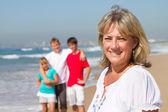 Szczęśliwe połowy wieku matki i rodziny na plaży — Zdjęcie stockowe