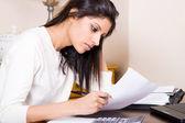 Beautiful woman doing finances at home — Stock Photo