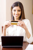 Beautiful young woman holding a credit card — Stock Photo