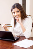 Confident young woman holding credit card — Stock Photo