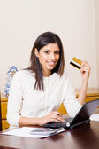 Pretty young woman holding a credit card — Stock Photo