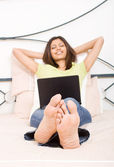 Young woman relaxing on bed with laptop — Stockfoto