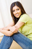 Young woman sitting on bedroom floor — Stock Photo