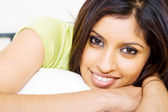 Beautiful young indian woman lying on bed — Stock Photo