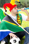 Soccer fan blowing a vuvuzela — Stock Photo
