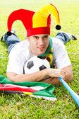 Soccer fan lying on green grass — Stock Photo