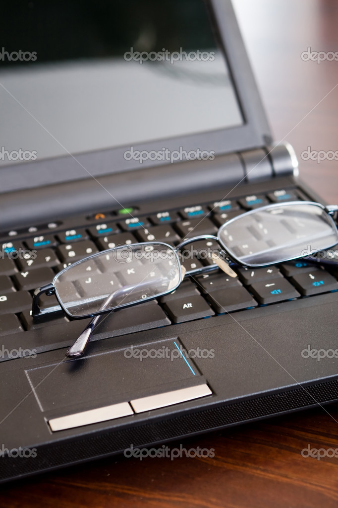 Glasses on black notebook computer — Stock Photo #11364104
