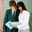 Female school teacher and student in classroom - Stockfoto