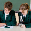 High schoool students using microscope — Stock Photo