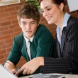 Female teacher teaching high school boy computer — Stock Photo