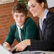 Stock Photo: Female teacher teaching high school boy computer