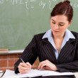 Female school teacher preparing lesson in classroom — Stock Photo