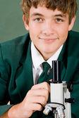 High school boy med mikroskop — Stockfoto