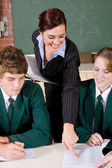 Female teacher helping high school students — Stock Photo