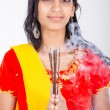 Stock Photo: Young indian woman holding incense