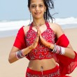 Young indian woman in traditional sari on beach praying — Stockfoto