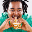 African american man eating hamburger — Stok fotoğraf