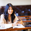 College student in lecture hall with mobile phone - Stockfoto