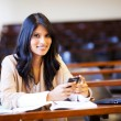 College student in lecture hall with mobile phone — Stock Photo