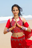 Young indian woman in traditional sari on beach praying — Stock Photo