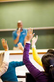 Students arms up in classroom — Zdjęcie stockowe
