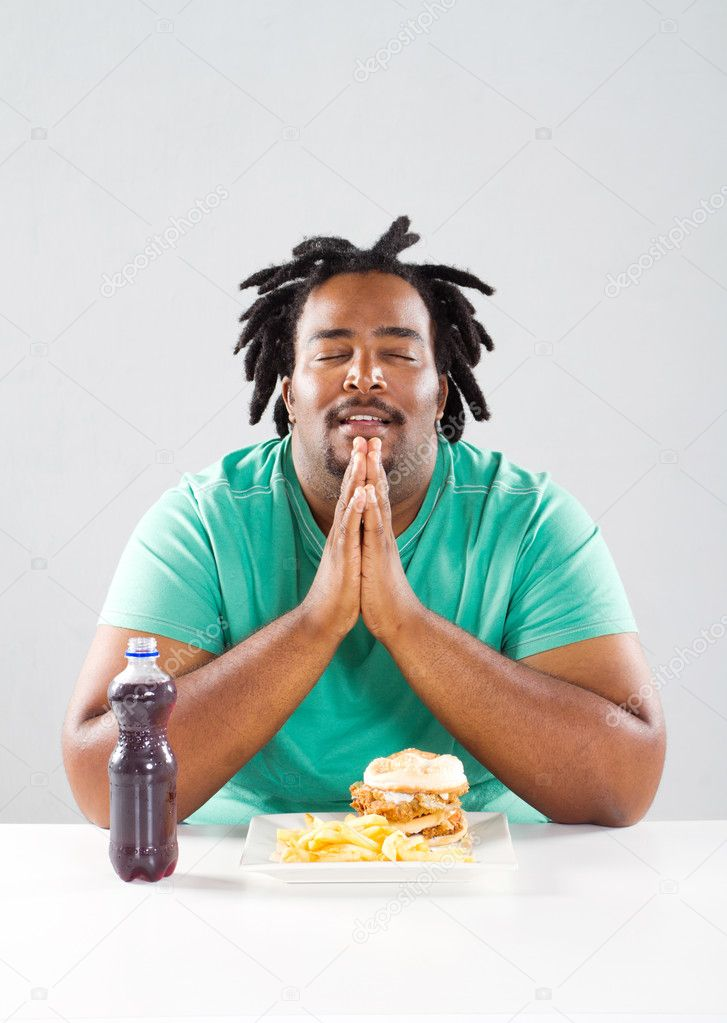 Overweight african american man pray before eating a meal — Stock Photo #11938879