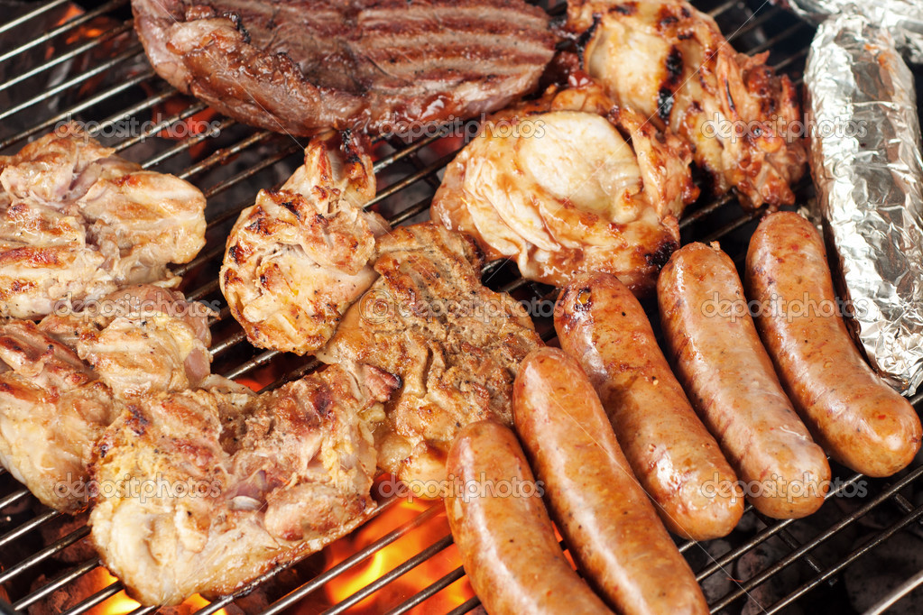 Various meats like chicken, sausage, steak and corn wrapped in aluminum foil on a barbecue grill — Photo #10803300