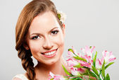 Beautiful young woman with a bouquet of flowers — Stock Photo