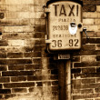 Vintage taxi sign on brick wall — Stock Photo