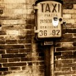 Stock Photo: Vintage taxi sign on brick wall