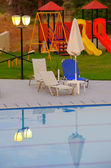 Poolside loungers and childrens playground — Stock Photo