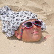 Boy buried in sand — Stock Photo