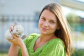 Happy girl with a rabbit in her arms — Stock Photo