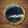 Ship porthole with storm outside - Stock Photo