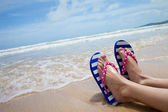 Young girl legs in colorful flipflop sandals on sea beach — Stock Photo