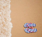 Colorful flipflop pair on sea beach top view — Stock Photo