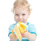 Happy pretty child eating banana. healthy food eating concept. — Stock Photo