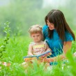 Stock Photo: Mother and daughter reading book together outdoor