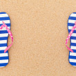 Colorful flipflop pairas a frame on beach sand — Stock Photo