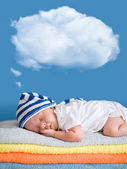 Little baby sleeping on stack of colorful towels with a dreaming — Stock Photo