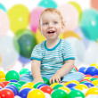 Cute boy playing colorful balls — Stock Photo