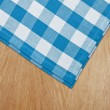 Wooden kitchen table with blue gingham tablecloth — Stock Photo