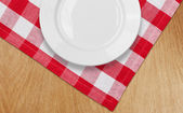 White plate on kitchen table with red checked tablecloth — Stock Photo