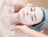 Beautiful woman with clear skin getting facial mask at salon — Stock Photo