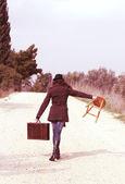 Chica con una maleta sentado en un taburete — Foto de Stock