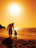 Father and daughter playing on the beach at sunset — Stock Photo