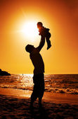 Father and daughter playing on the beach at sunset — Foto Stock